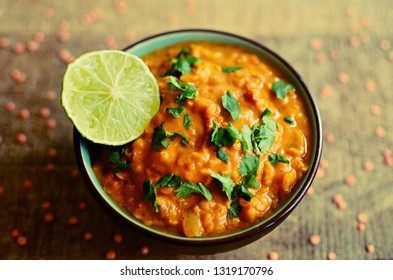 Red lentils dahl bowl with lime and fresh coriander, wooden background