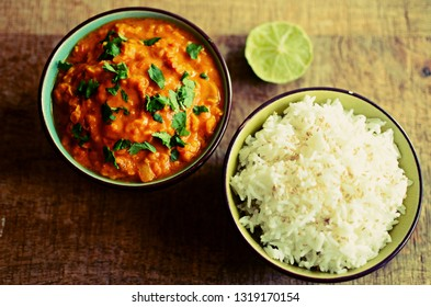 Red lentils dahl and rice bowls with line and fresh coriander, wooden background
