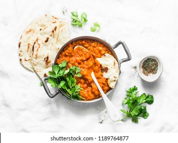 Red lentils dhal and paratha flatbread - healthy vegetarian dinner in Indian style on light background, top view