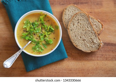 Red lentils soup with spices and salad