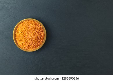 Red lentils in wooden plate on black stone table background. Top view, copy space.