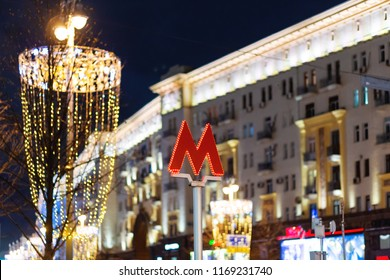 Red letter M - symbol of Moscow subway (metro). Street decorated with light bulbs for New Year and Christmas celebration. Winter evening. Russia.