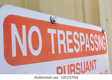 Red lettered no trespassing sign. Fastened to a corrugated steel building this closeup emphasizes the words NO TRESPASSING.