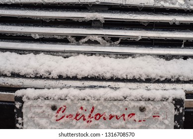 red lettering script word spells California under new fallen snow on a car license plate  front of car in winter in California