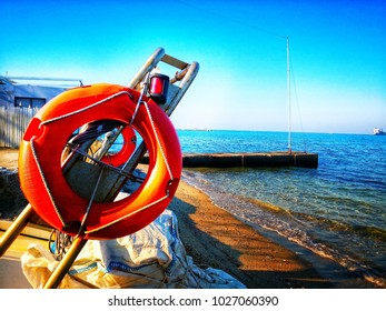 Red life ring in the Thessaloniki harbour, view on the sea, marine equipment
