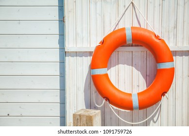 red lifebuoy on a white wooden wall. Background, copyspace