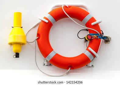 Red lifebuoy with rope on white ship wall