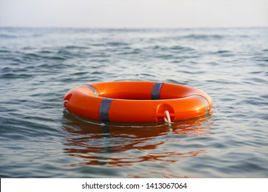 Red lifebuoy in sea on water.