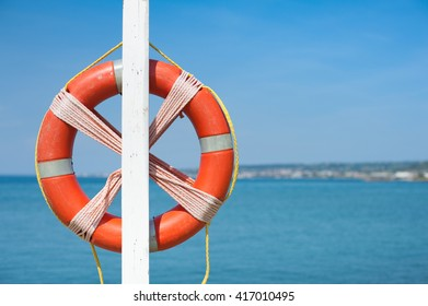 Red lifebuoy symbol of safety close up on empty out of focus blue sea in background