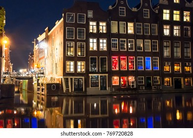 Red light district at night with illuminated medieval buildings in  Amsterdam city center, the Netherlands.
