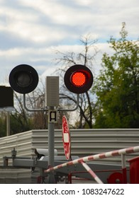 the red light of the semaphore, which prohibits the passage of vehicles over the railroad tracks waiting for a train