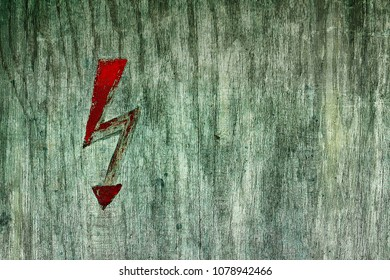Red light sign indicating electricity on a wooden board