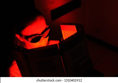 red light therapy. The girl goes through a course of skin rejuvenation with the help of red light treatment.