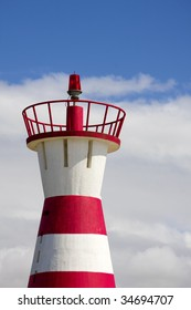 red lighthouse  in blue sky with white clouds