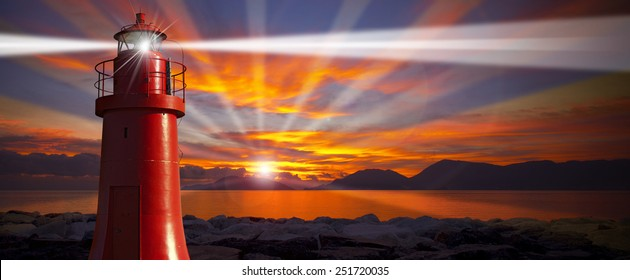Red Lighthouse with Light Beam at Sunset. Red and metallic lighthouse with light beam at sunset with clouds