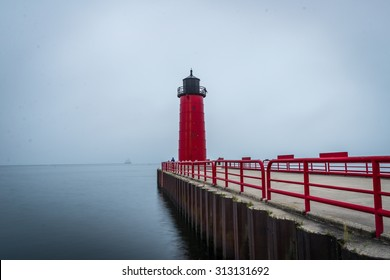 Red Lighthouse on Lake Michigan in the early morning hours of a foggy day