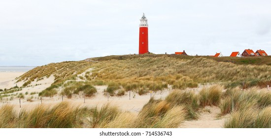 Red lighthouse on the Texel island in the Netherlands. Lighthouse in dunes, houses with red roofs on the nothern sea shore