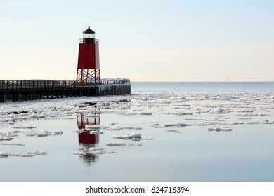 A red lighthouse reflects in calm water dotted with floating chunks of ice.