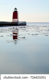 A red lighthouse reflects into calm water with chunks of ice.
