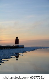 A red lighthouse reflects into a partially iced over lake at sunset.