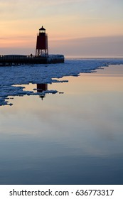 A red lighthouse reflects into a partially iced over lake at sunset with water in the foreground.