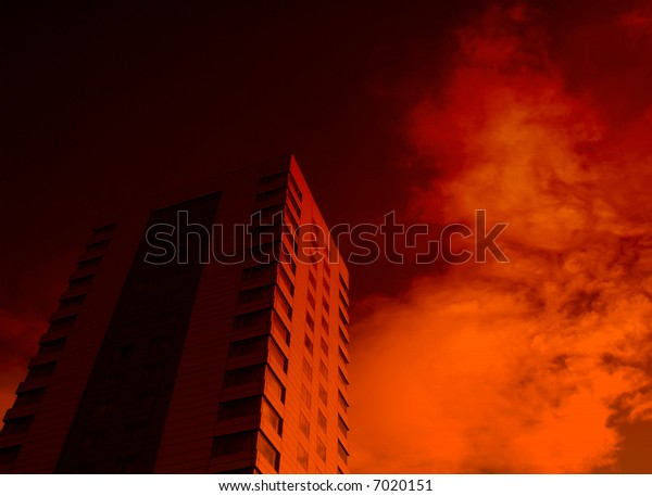 Red lighting effect applied to office building against cloudy sky giving menacing effect.
