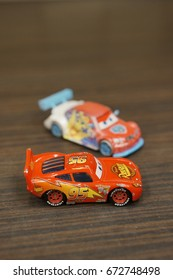 Red Lightning McQueen main character from the Disney Pixar movie Cars on wooden surface in soft focus on July 2017 in Poznan, Poland. Collection belongs to the toy company Mattel Inc.