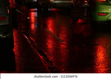 Red lights reflecting on the wet road at night