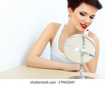 Red lips. Beautiful Woman Doing Daily Makeup. Lipstick applying