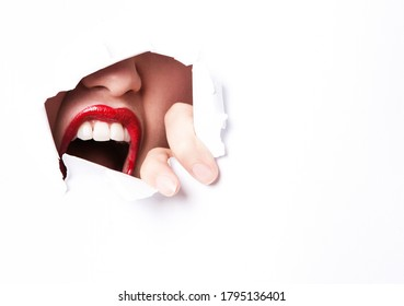 Red Lips and mouth peering through ripped paper