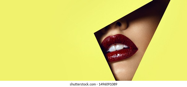 Red lips peep through a hole in yellow paper. Beautiful white teeth.