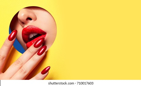Red lips peep through the hole in the yellow paper. Fingers at the mouth with bright red manicure.Lipstick, cosmetics, makeup, nail polish, beautiful fingers, fashion, beauty.Fashion, beauty, make-up.