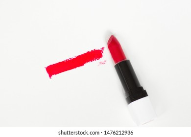 Red lipstick bullet smudged isolated on white with copy space.