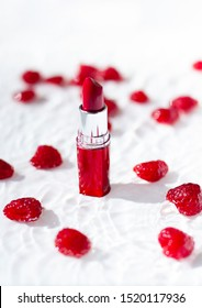 Red  lipstick bullet in transparent water with swimming raspberries. Close up