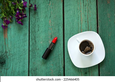 Red Lipstick and cup of coffee on wooden table decorated violet flowers and berries