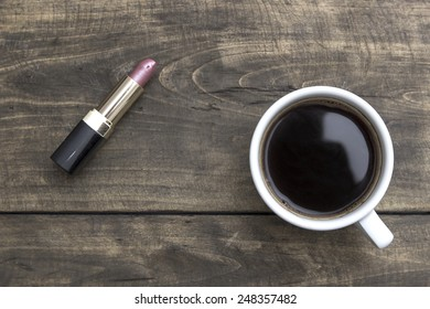 Red Lipstick and cup of coffee on wooden table, from above