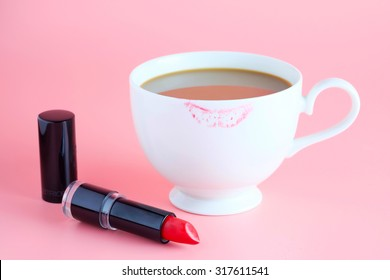 red lipstick and cup of coffee on pink background