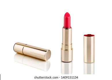 Red lipstick in golden tube on white background with mirror reflection on glass surface isolated close up, shiny gold lipstick package, open and closed lipsticks box, luxury cosmetic accessory set
