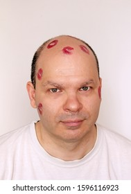 Red lipstick kisses marks on young man with bold head