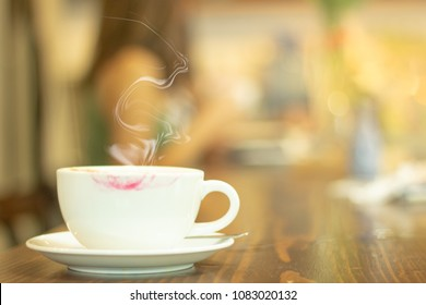 red lipstick mark on hot coffee cup with smoke on wooden table