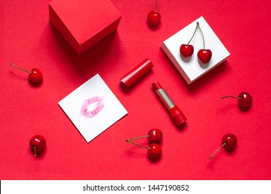 Red lipstick on the red background with ripe cherries . Valentines day concept card Top view