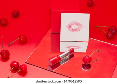 Red lipstick on the red background with ripe cherries and a lip kiss on the paper. Valentines day concept card