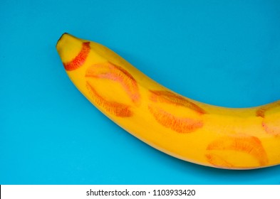 red lipstick on a banana on blue background. concept oral sex