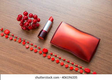 Red lipstick and powder box on a wooden background. Women's accessories on a wooden desk.