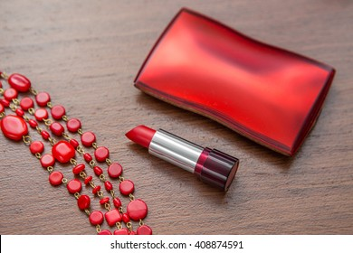 Red lipstick and powder box on a wooden background