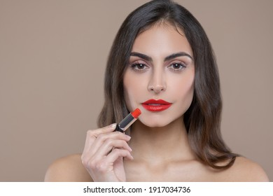 Red lipstick. Serious beautiful face of dark haired woman with brown eyes with red lipstick on her lips