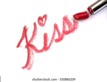 """Red lipstick writing """"Kiss"""" on white surface"""