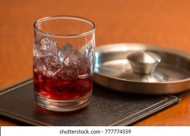 Red Liquor On Ice on Squre Leather Coaster with Metal Lid on the background