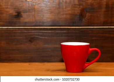 Red little cup on wooden background
