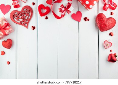 Red little hearts on white wooden background with copy space. Wooden Background for design to Valentine's Day. Decorative red hearts. View from above. Valentines Day concept